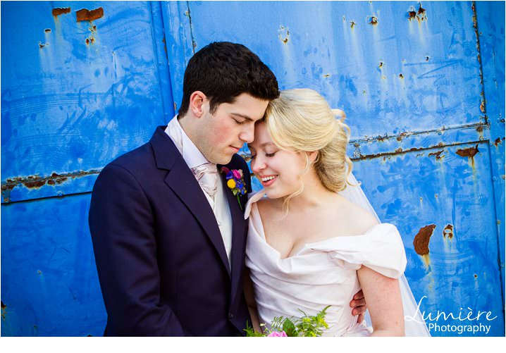 Eversholt Hall wedding : Bride and groom in front of blue background