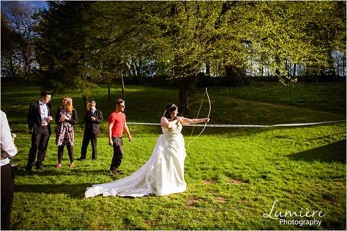 Bride shooting arrows at Hargate Hall wedding