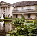 Bride and groom in front of a very classical Derbyshire wedding venue with reflection in the pond